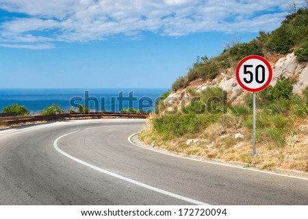 Round speed limit road sign on the road - stock photo