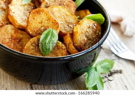 Round spicy baked potatoes with condiments and basil leaves,selective focus - stock photo