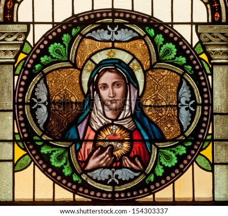 Round stained glass window depicting Immaculate Heart of Mary