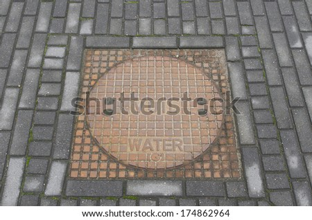 round steel manhole cover with dirty water written on it - stock photo