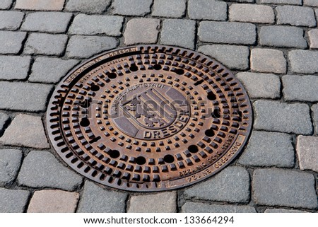 Round steel sewer manhole on pavement in Dresden - stock photo