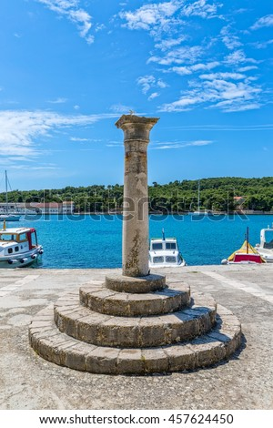 Round stone bench in the Prvic Luka town port at beautiful summer day in Croatia.