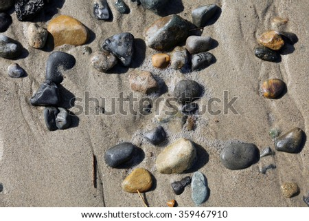 Round stones and rocks smoothed by the ocean, waves and tides lay piled in the sand on the beach. Rocks of various types of minerals can be found on the beach. - stock photo