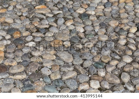 Round stones in the ground. Texture of the cobblestones in Park. Paved road for pedestrians. The paving stones. Background - stock photo