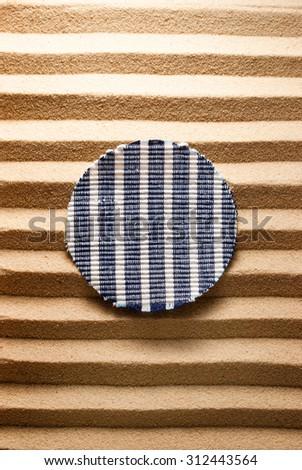 Round striped cloth on a striped sandy background. - stock photo