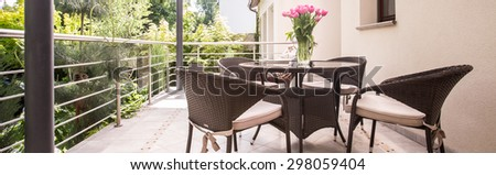 Round table and wicker armchairs on the verandah - stock photo