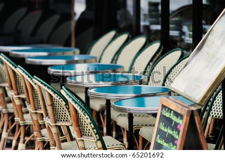 Round tables and wicker chairs in cafe in Paris. Photo with tilt-shift effect - stock photo