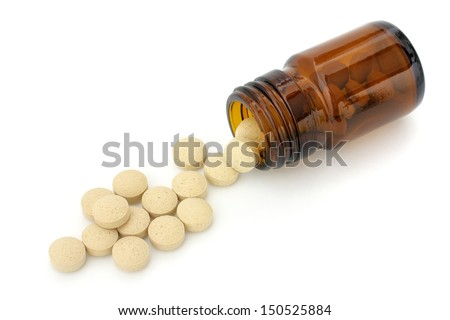 Round tablets spilling out of brown small bottle isolated on white background - stock photo