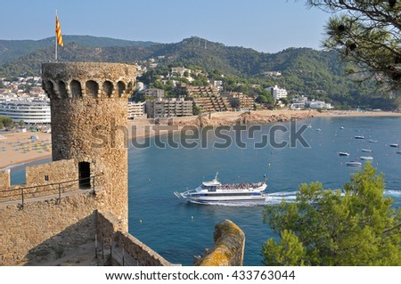 Round Tower and boat entering the bay of Tossa de Mar in Costa Brava , Gerona