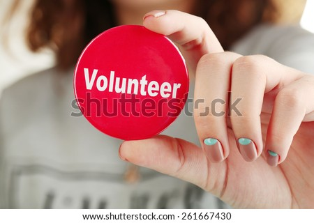 Round volunteer button in hand close-up - stock photo
