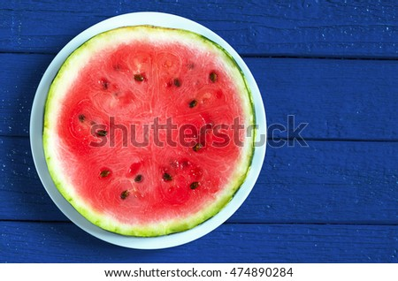 Round watermelon slice in plate on dark blue wooden background, top view
