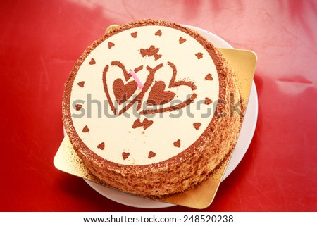 round white and brown cake decorated with two chocolate hearts and one candle gift for Valentine day - stock photo