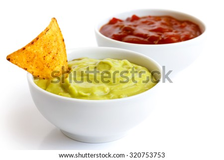 Round white bowl of guacamole dip isolated in perspective. Tortilla chip in dip. Bowl of tomato salsa in background.