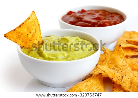 Round white bowl of guacamole dip isolated in perspective. Tortilla chips around and in dip. Bowl of tomato salsa in background.