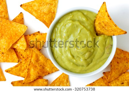 Round white bowl of guacamole dip with tortilla chips inside and surrounding, isolated from above.