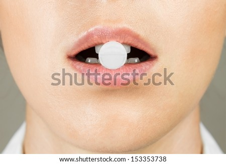 Round white pill in woman's mouth, close-up - stock photo
