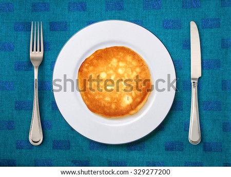 round white plate with cake, knife and fork on table  - stock photo