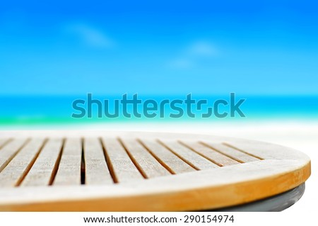 Round wood table top on blur blue sea and sky background - can be used for display or  montage your products - stock photo