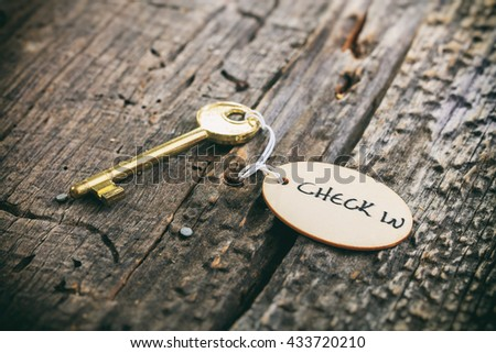 """Round wooden tag with """"Hotel"""" text on a key, on wooden surface - stock photo"""