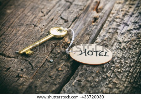 "Round wooden tag with ""Hotel"" text on a key, wooden surface - stock photo"
