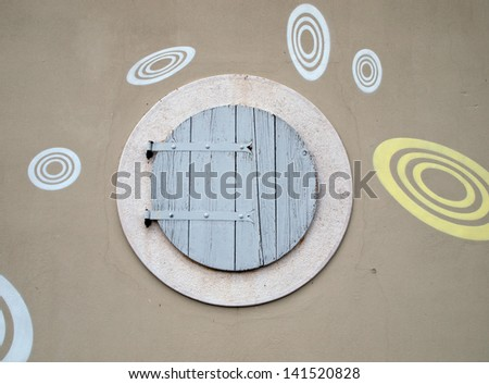 round wooden window on building facade - stock photo
