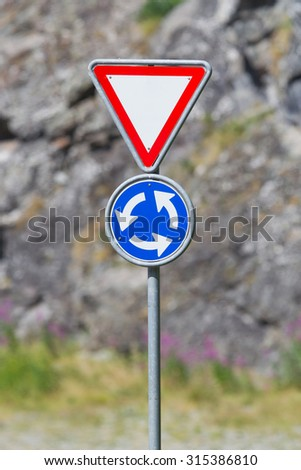 Roundabout crossroad road traffic sign, blue, white arrows right hand - stock photo