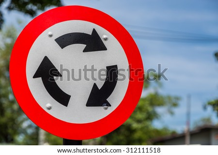 Roundabout Road Sign for Traffic with green bokeh background - stock photo