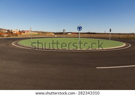 Roundabout roundabout or new construction. Designed to simulate grass green painted cement. Outside urban space. With vertical traffic signs and corresponding asphalt  - stock photo