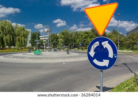 Roundabout with a clock and sign before - stock photo