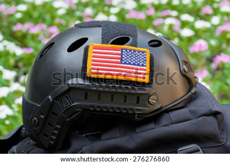 Rounded American flag patch stick on side of Special force Modern combat helmet with purple flower background - stock photo