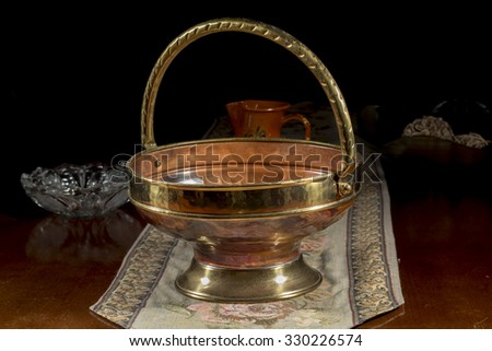 Rounded centerpiece of bronze on an embroidered table mat