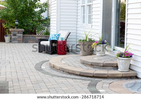 Rounded Steps to Back Door of Luxury Home, Stone Patio with Comfortable Wicker Furniture and Flower Pots - stock photo