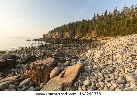 Rounded stones nestled in larger rocks on Boulder Beach looking toward the Otter Cliffs at sunrise in Acadia National Park, Maine