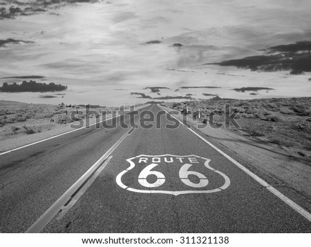 Route 66 pavement sign black and white in California's Mojave desert.