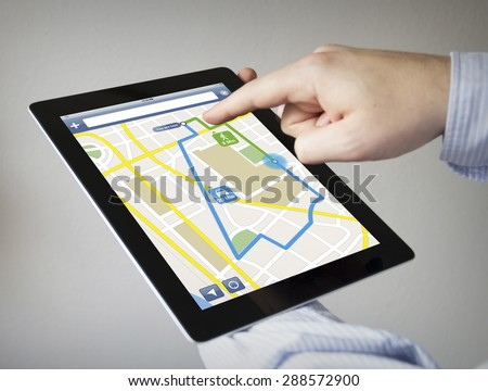 route planner concept: hands with touchscreen tablet with gps navigation app on the screen. Screen graphics are made up.  - stock photo