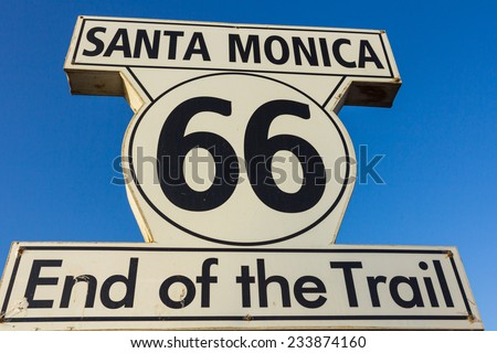 Route 66 sign at Santa Monica Pier over blue sky in the background.