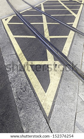Routes of tram in the city, detail of an urban transport circulation signal, asphalt and city transport - stock photo