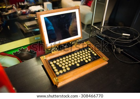 ROVANIEMI/FINLAND - FEBRUARY 25, 2013; The Santa Park. Tablet in the wooden cover and vintage keyboard.
