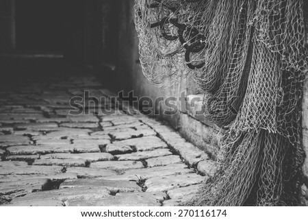 Rovinj old town, Croatia. Fishing nets hanging on the door. Black and white photo. - stock photo