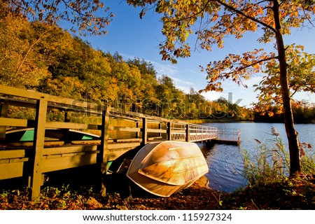 Row boat against wood dock in golden afternoon light - stock photo