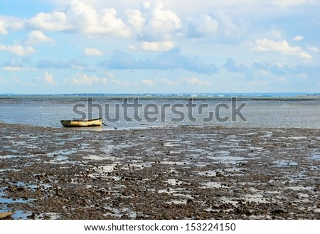 Row boat at the shoreline during low tide - stock photo