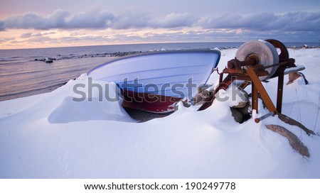 Row boat laying on a stone beach next to the waterduring a cold winter.GN - stock photo