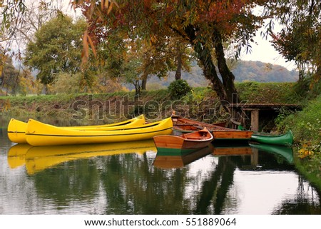 Row boats by the autumn river Krka, Slovenia.
