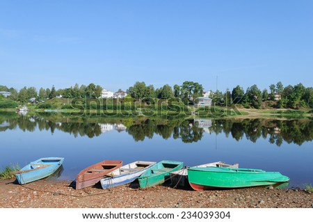 Row boats on the bank of Sukhona river in Totma town, Northern Russia. Quiet windless morning - stock photo