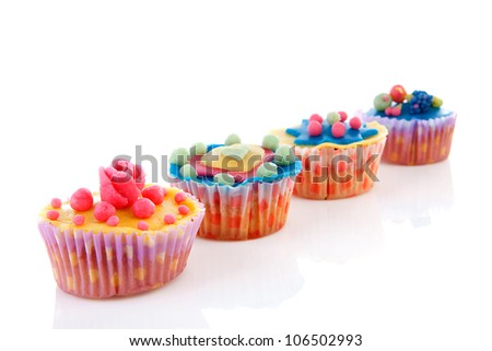 Row cupcakes with colorful marzipan decoration over white background