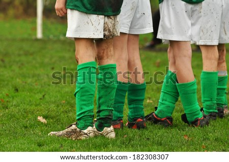 Row legs of soccer playing kids waiting for a penalty