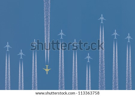 Row of airplanes flying by with one in the opposite direction