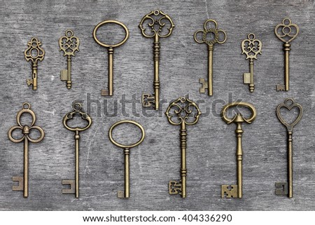 row of antique golden keys on a grunge wooden background - stock photo