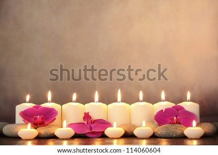 Row of aromatic candles and orchid petals. - stock photo