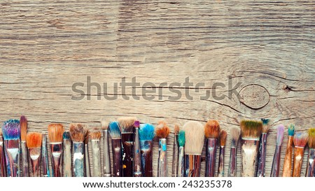 Row of artist paintbrushes closeup on old wooden rustic background - stock photo
